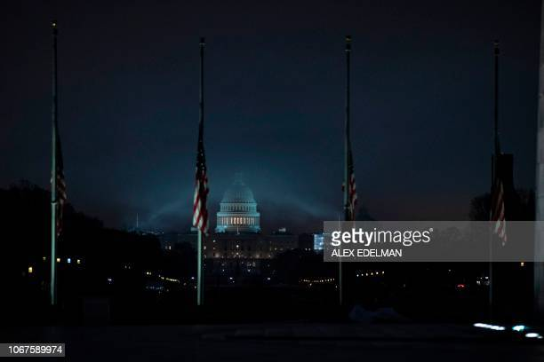 TOPSHOT The US flag flies at halfstaff in front of the Washington Monument and US Capitol in tribute to former US President George H W Bush early on...