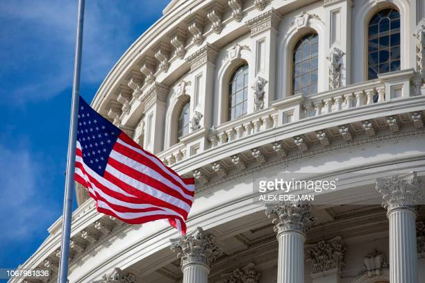 The US flag flies at halfstaff in honor of former US President George HW Bush outside the US Capitol in Washington DC on December 3 2018 Bush died on...