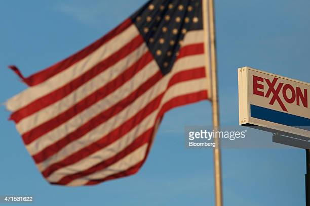The US flag flies near Exxon Mobil Corp signage displayed at a gas station in Richmond Kentucky US on Wednesday April 29 2015 Exxon Mobil Corp is...