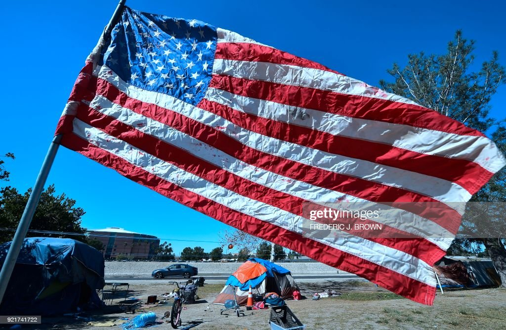 TOPSHOT - The US flag flies near homeless tent at atenc&ment beside the Santa Ana River & TOPSHOT - The US flag flies near homeless tent at atencampment ...