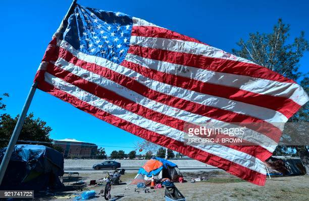 TOPSHOT The US flag flies near homeless tent at atencampment beside the Santa Ana River in Anaheim California on February 20 2018 Officials in Orange...