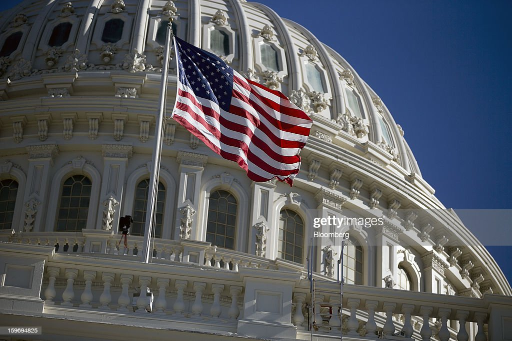 The U.S. flag flies outside of the U.S. Capitol prior to the second inauguration of U.S. President Barack Obama in Washington, D.C., U.S., on Friday, Jan. 18, 2013. President Obama's second inauguration next week will combine the star power of Beyonce, Kelly Clarkson and James Taylor with a lineup that reflects social values Obama will champion in his new term. Photographer: Andrew Harrer/Bloomberg via Getty Images