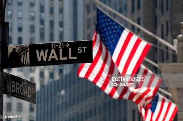 The US flag flies outside the New York Stock Exchange on March 11 2019 in New York The benchmark Dow Jones Industrial Average was flat midmorning...
