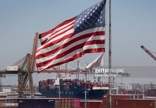 The US flag flies over a container ship unloading it's cargo from Asia at the Port of Long Beach California on August 1 2019 President Donald Trump...