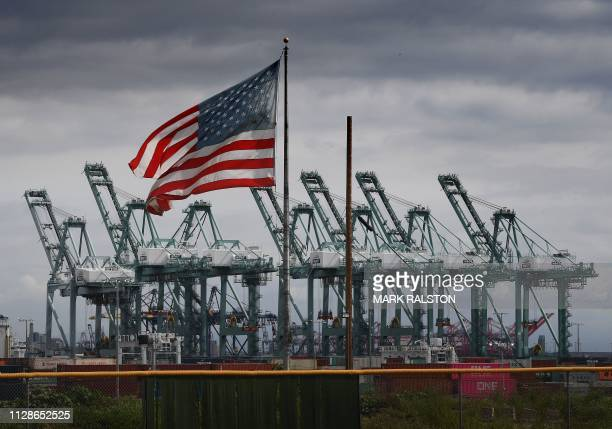 TOPSHOT The US flag flies over shipping cranes and containers after a report said the United States and China are close to reaching a major trade...