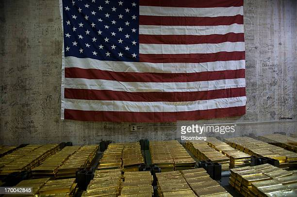 The US flag hangs over gold bars in a vault at the United States Mint at West Point in West Point New York US on Wednesday June 5 2013 Sales of gold...