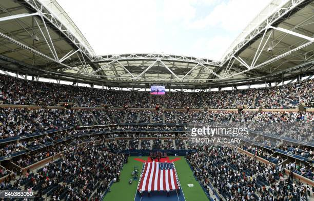 The US flag is brought to centre court before the start of the 2017 US Open Men's Singles final match between South Africa's Kevin Anderson and...