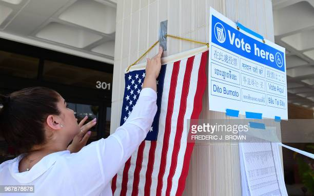 The US flag is displayed beside signs posted outside a polling station at the Alhambra Fire Department in Alhambra Los Angeles County California on...