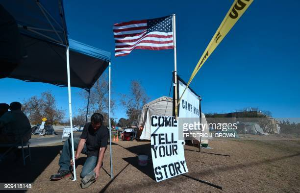 TOPSHOT The US flag is hoisted at Camp Hope a homeless encampment near the Honda Center in Anaheim California on January 23 2018 January 22 reports...