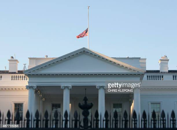 The US flag over the White House in Washington DC flies at halfstaff on September 11 on the 14th anniversary of the 9/11 attacks AFP PHOTO/CHRIS...