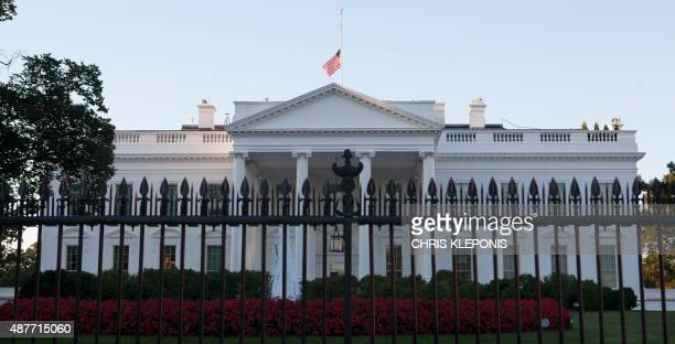 The US flag over the White House in Washington, DC, flies at half-staff on September 11 on the 14th anniversary of the 9/11 attacks. AFP PHOTO/CHRIS...