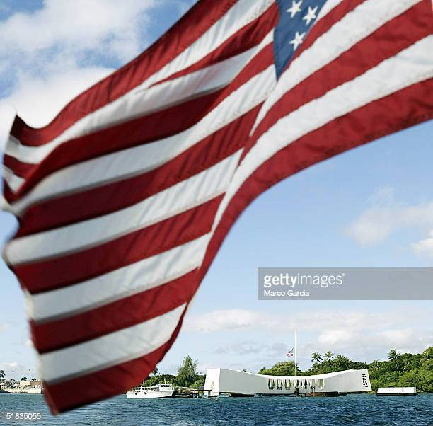 The US flag waves in the wind from the back of a ferry as the USS Arizona Memorial looms in the background December 7 2004 in Pearl Harbor Hawaii...