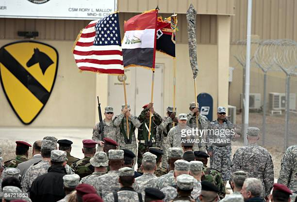The US Iraqi and division flags are held up during a handing over ceremony by the 4th Infantry Division to the 1st Cavalry Division held at Camp...