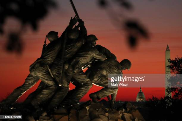 The US Marine Corp's Iwo Jima Memorial can be seen as the morning sun begins to rise behind the US Capitol and Washington Monument on Veterans Day...