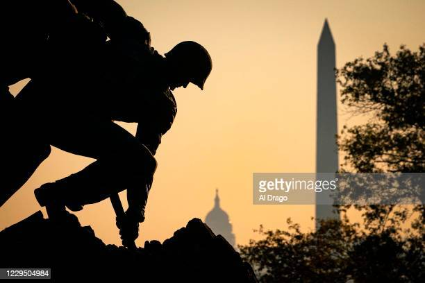 The U.S. Marine Corp's Iwo Jima Memorial can be seen as the morning sun begins to rise behind the U.S. Capitol and Washington Monument on November 7,...