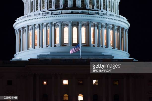 The US National flag flies at halfmast in front of the United States Capitol building in Washington a few hours after the death of US Republican...