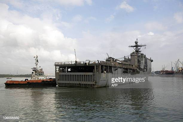 The US Navy ship the USS Pearl Harbor is pushed by a Kenyan tug boat as it docks in the port of Mombasa on November 5 2010 after some 68 Ethiopian...