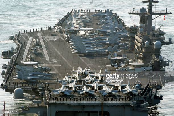 The US Navy's nuclearpowered aircraft carrier Carl Vinson arrives at the port of Busan South Korea on March 15 for ongoing joint military drills with...