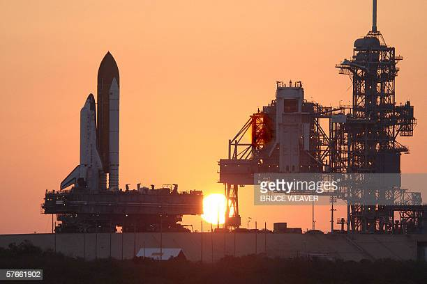 The US space shuttle Discovery with its external tank and twin solid rocket boosters is silhouetted 19 May 2006 at sunset as it moves up launch pad...