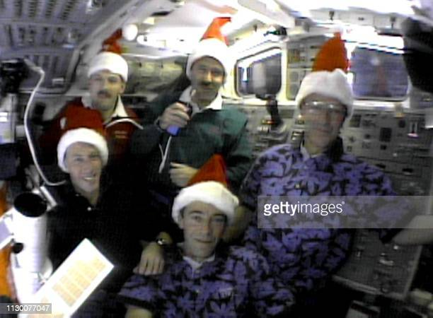 The US space shuttle Discovery's crew wear Santa Claus hats during an onorbit media interview 25 December 1999 from the shuttle's aft flight deck...