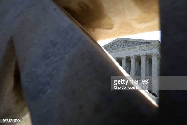 The US Supreme Court is seen through the stone balcony that rings the building June 18 2018 in Washington DC The court handed down opinions in five...