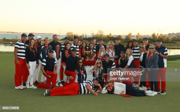 The US Team and their wives and girlfriends pose with the Presidents Cup trophy during the Sunday singles matches at the Presidents Cup at Liberty...