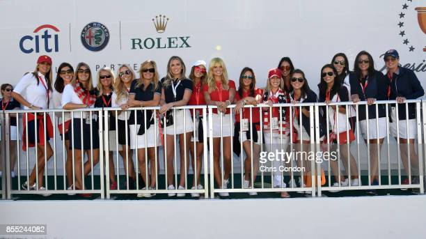 The US Team wives and girlfriends pose for a photo during the trophy presentation during the first round of the Presidents Cup at Liberty National...