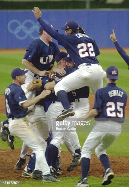 The USA baseball team mobs pitcher Ben Sheets on the mound after winning 40 over Cuba for the gold medal