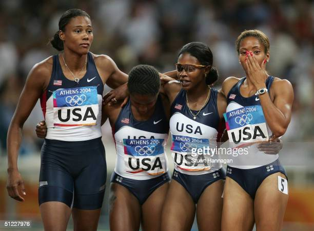 The USA relay team Marion Jones Lauryn Williams Angela Williams and LaTasha Colander walk dejected after the women's 4 x 100 metre relay on August 27...