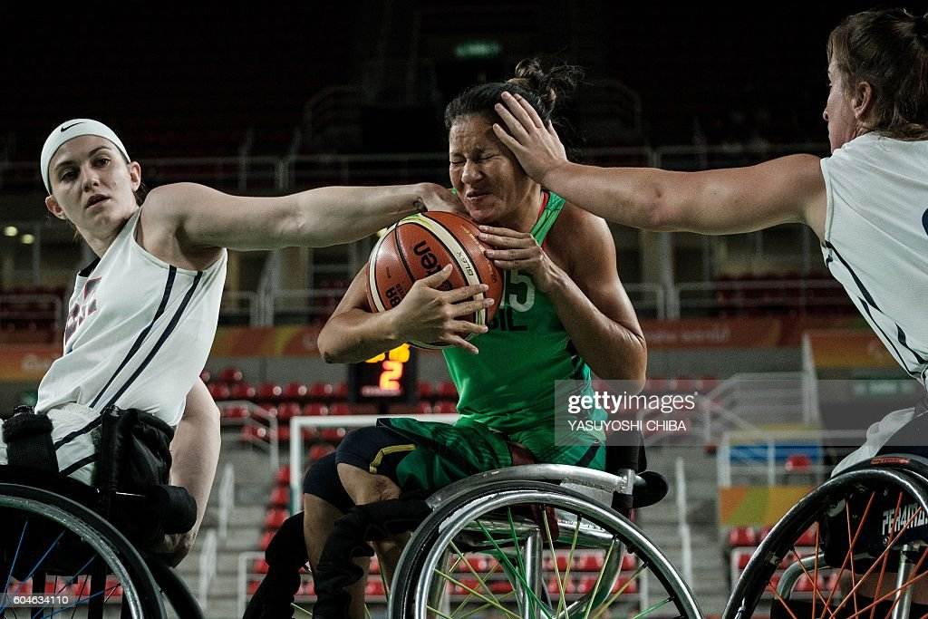 TOPSHOT - The USA's Desiree Miller (L) and Gail Gaeng (R) block Brazil's Vileide Almeida during the women's wheelchair basketball quarterfinal in the Paralympic Games at Olympic Park in Rio de Janeiro on September 13, 2016. / AFP / YASUYOSHI