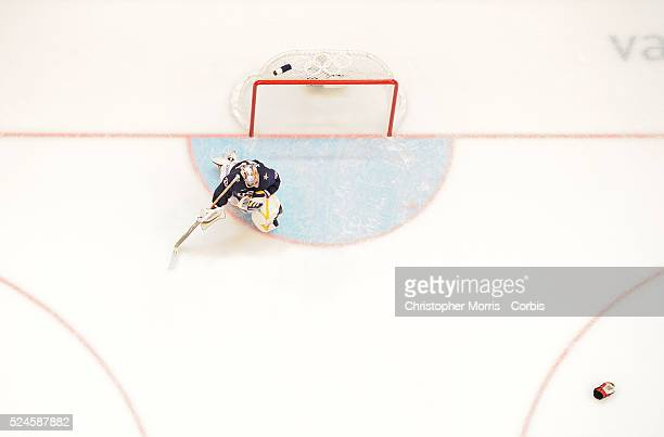 The USA's goaltender Ryan Miller kneels in front of the net after letting in the winning goal in overtime of the gold medal game between Canada and...