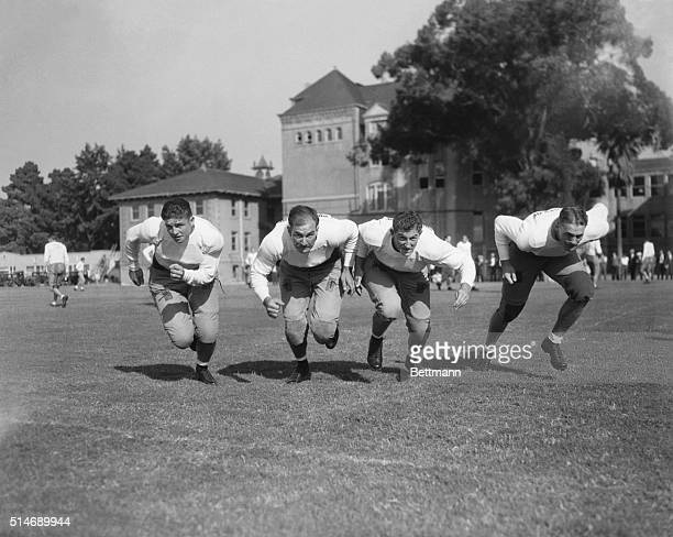 The USC football team rushes towards the camera. From left to right are R. Brown, Ernie Smith, Aaron Rosenberg, and Bob Hall.
