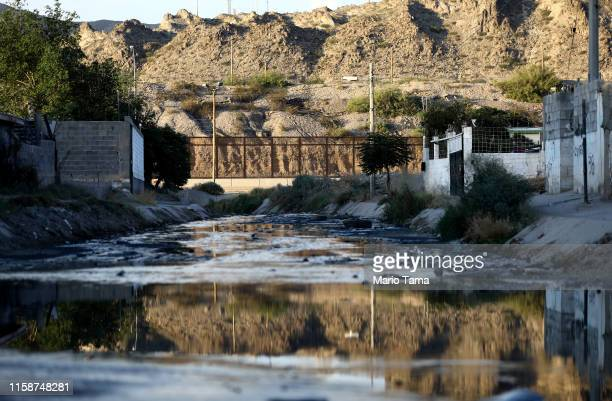 The USMexico border barrier stands beyond an undrained street on June 27 in Ciudad Juarez Mexico According to US Customs and Border Protection...