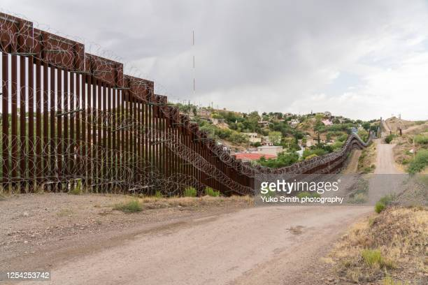 the us/mexico border fence in nogales, arizona usa - geographical border stock pictures, royalty-free photos & images