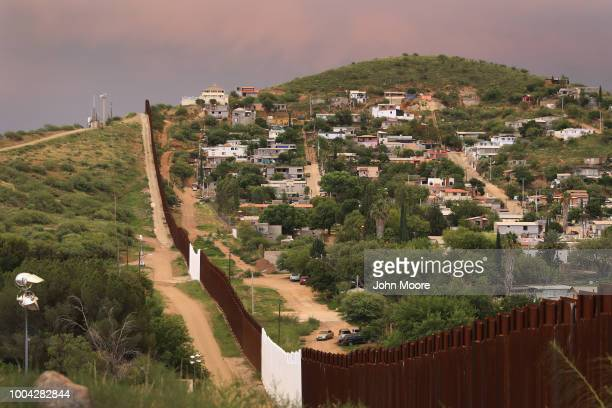 The USMexico border fence is seen at sunset on July 22 2018 in Nogales Arizona On right is Nogales Mexico Security cameras are seen mounted on towers...