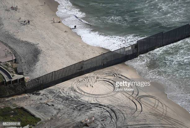 The USMexico border fence seen from above stretches into the Pacific Ocean on May 11 2017 in San Diego California The fence separates San Diego...