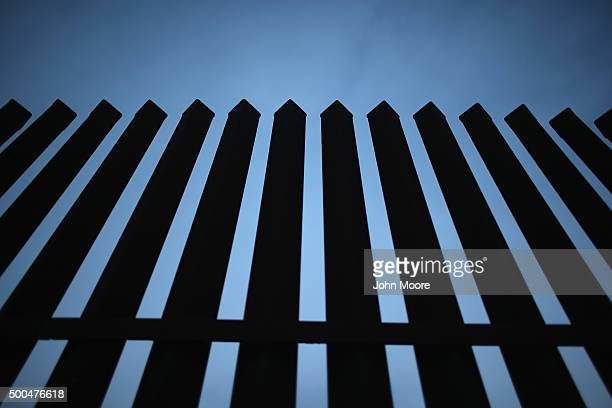 The USMexico border fence stands on December 8 2015 near McAllen Texas The number of migrant families and unaccompanied minors has again surged in...
