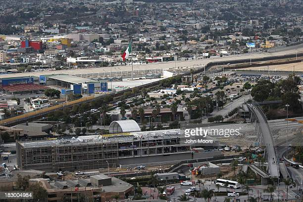 The USMexico border fence stretches through the port of entry in Mexico on October 3 2013 at the San Ysidro California While hundreds of thousands of...