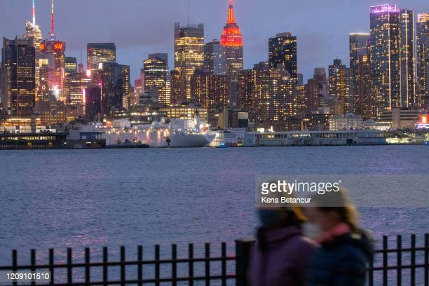 The USNS Comfort navy hospital ship is docked at Pier 90 as The Empire State Building Glows Red In Solidarity With Those Infected With COVID-19 on...