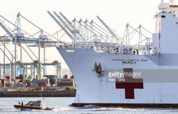 The USNS Mercy Navy hospital ship passes shipping cranes as it arrives in the Port of Los Angeles to assist with the coronavirus pandemic on March 27...