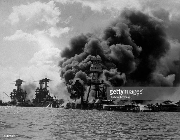 The USS Arizona burning furiously in Pearl Harbour after the Japanese attack. To the left of her are USS Tennessee and the sunken USS West Virginia.