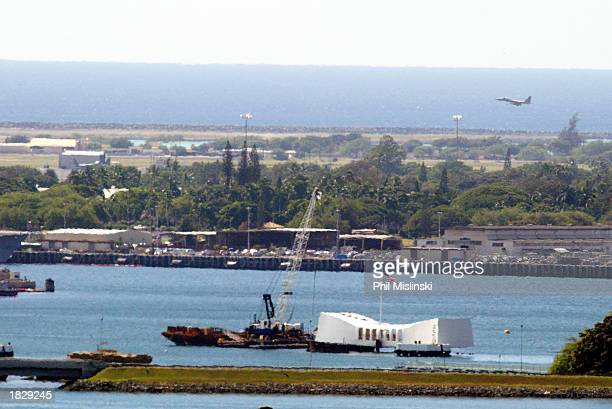 The USS Arizona Memorial is seen in the foreground as a US military jet lands at Honolulu International Airport March 4 2003 on Oahu Hawaii...