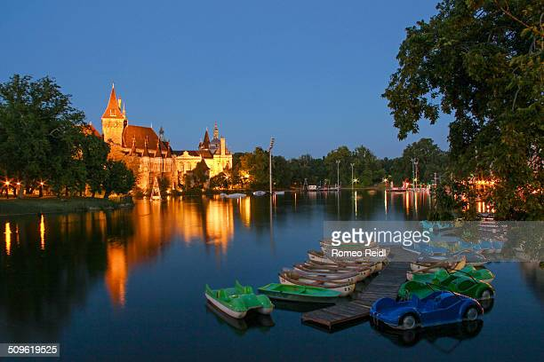 The Vajdahunyad castle photographed from the Budapest City Park with the boating lake at nightfall.