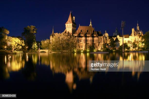 The Vajdahunyad Castle reflects in the boating lake on a summer night in the City Park of Budapest, Hungary.