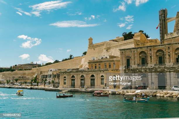 the valletta waterfront and the old city seen from a boat - valletta stock pictures, royalty-free photos & images