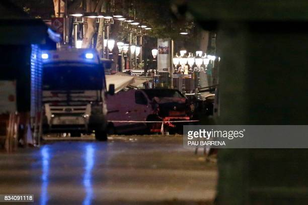 TOPSHOT The van who ploughed into the crowd killing at least 13 people and injuring around 100 others is towed away from the Rambla in Barcelona on...