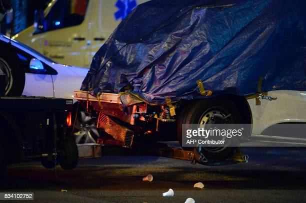 The van who ploughed into the crowd killing at least 13 people and injuring around 100 others is towed away from the Rambla in Barcelona on August 18...