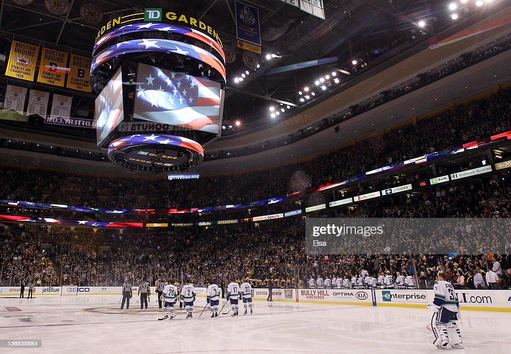The Vancouver Canucks and the Boston Bruins stand before the game as the national anthems are sung on January 7, 2012 at TD Garden in Boston, Massachusetts.