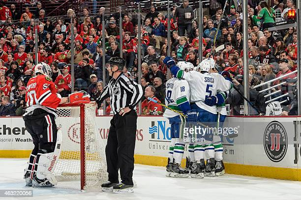 The Vancouver Canucks celebrate behind goalie Corey Crawford of the Chicago Blackhawks after scoring their third goal in the second period during the...
