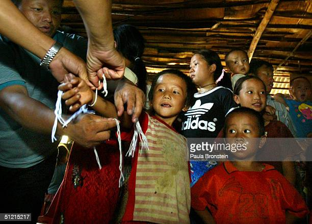The Vang family go through a ritual as a shaman hands them strings to tie on their wrists during a good luck ceremony shortly before the family gets...